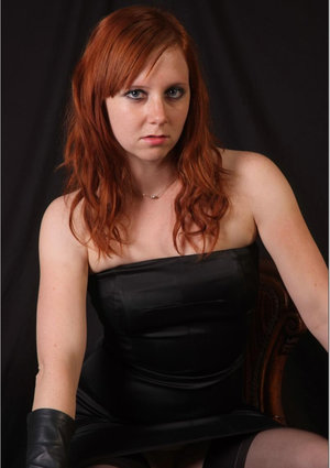 Natural redhead holds a cane with leather gloves while exposing her pink slit