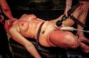 Blond sub Layla Price is restrained before lesbians penetrate her in a dungeon