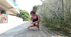 White girl pulls down her panties before squatting for a piss on country road
