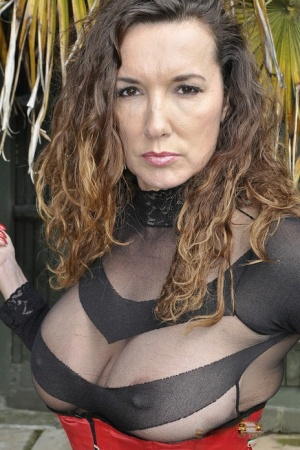 A clothed Strapon Jane flaunts her strapon cock in garden wearing see thru top 70012404