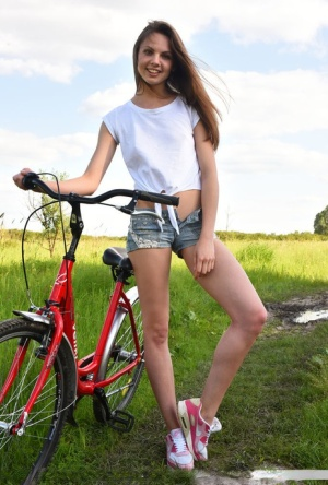 Cheeky brunette Cheyanna drops her shorts to pose nude with her bicycle