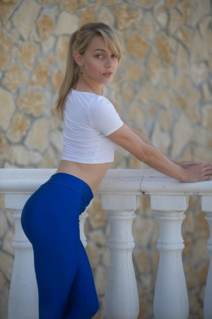 Young blonde girl Chloe Toy pulls down her blue yoga pants on the balcony