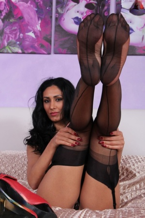 Brunette chick kicks off her heels before rubbing a dildo with nylon clad feet