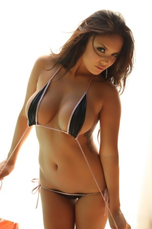 Solo model Justene Jaro places hands over huge boobs after removing bikini top