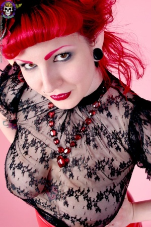 Redhead model Xanthia Doll poses non nude in see thru blouse and latex skirt