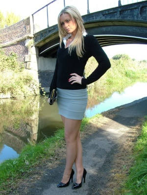 Non nude blonde shows off sexy legs in miniskirt and black pumps on foot path