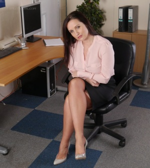 Clothed female shows off her stiletto heels in tan nylons and a skirt