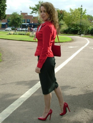 Mature woman crosses her hose covered legs in a long skirt and red pumps