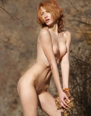 Skinny redhead Mila F wraps herself in a scarf on a fall day while posing nude