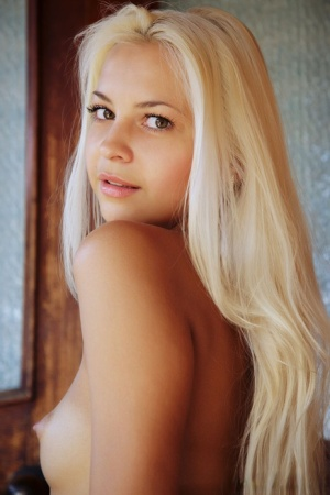 Sexy blonde model rids herself of a summer dress for nude solo posing