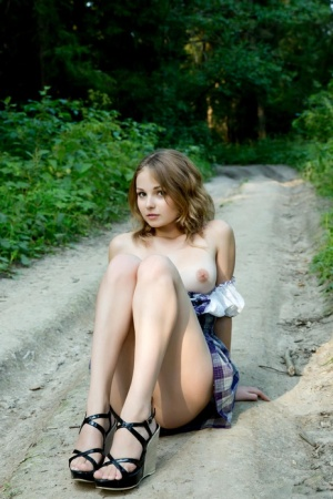 Young blonde girl Jeff Milton hikes up her skirt on path in the woods
