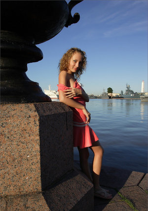 Curly haired girl exposes her pussy and small tits while hanging out on a pier