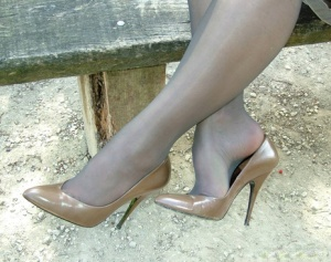 Fully clothed blonde beauty shows off her new pumps in garden wearing nylons