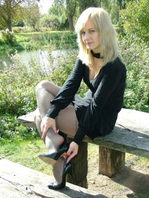 Blonde seductress models her sexy feet and long legs wearing heels in the park