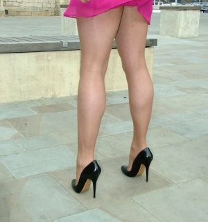 Woman showing off her nice legs and sexy feet in stockings  heels outdoors
