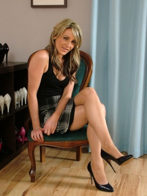 Solo model shows off her nice legs in tartan skirt and high heeled shoes