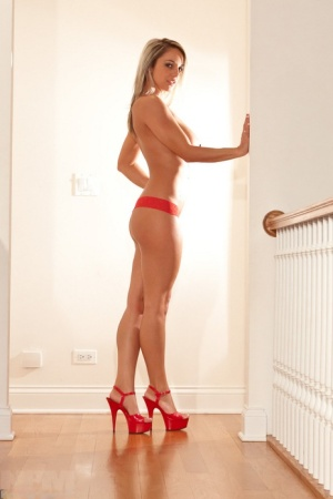 Leggy blonde chick Nikki Sims covers her bare boobs while posing in a thong