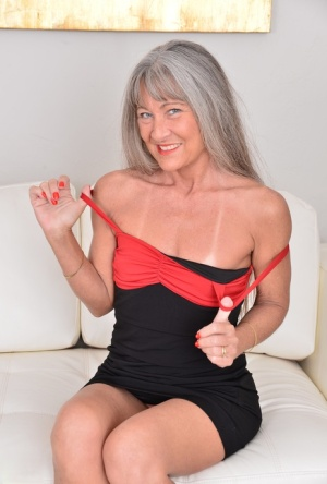 Older woman with grey hair uncovers her flat chest while undressing