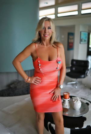 Leggy housewife with blonde hair lets a huge boob free from tight dress