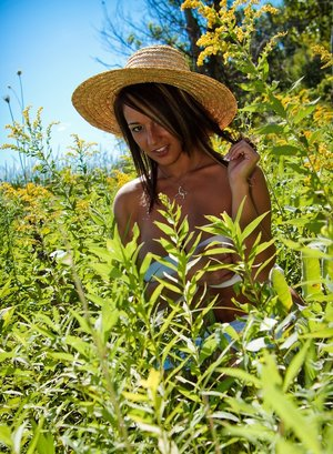 Dirty blond Nikki Sims covers bare breasts while wearing a sun hat in a field