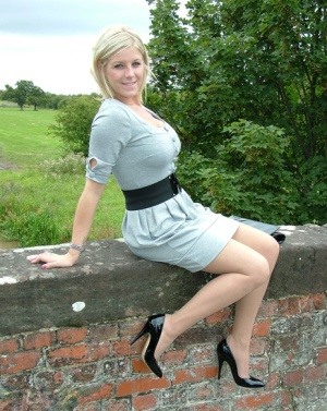 Blonde female sits atop a bridge in a dress and nylons with shiny pumps
