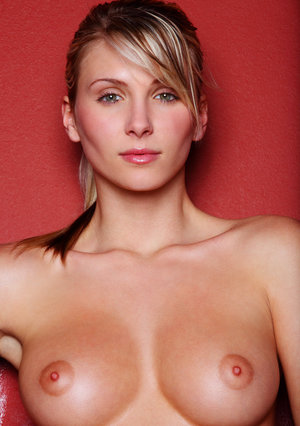 Dirty blond beauty Nicole strikes great nude poses while up against a red wall
