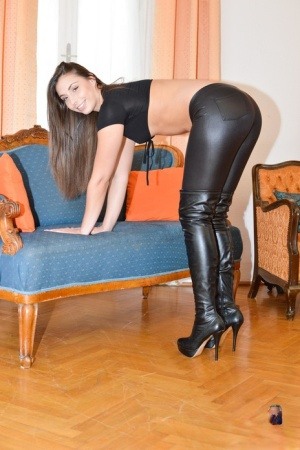 Hot brunette Carla in tight leather pants spreading ass on the couch