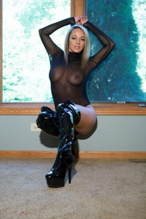 Sexy slender Nikki Sims rubbing her bare pussy in latex and high boots