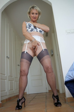 Mature housewife Michelles Nylons fondles her big tits and gives a POV handjob
