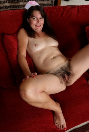 Older nurse Sherry Lee puts her natural pussy on display upon a red sofa