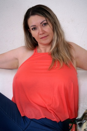 Overweight housewife holds her big breasts as she takes off all her clothes