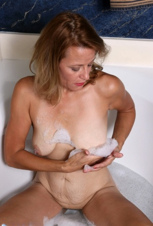 Mature housewife Jade Allan plays with bald pussy while taking a bath