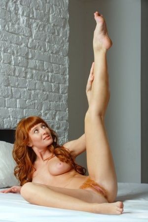 Cute redhead Ossana spreading nude to reveal her matching hairy pussy