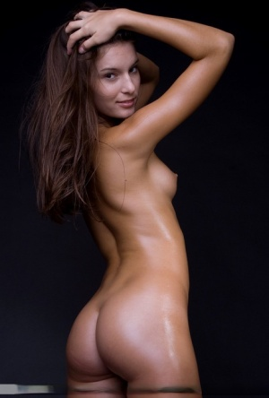 Solo model Nikki D shows off her oil slicked body while totally naked