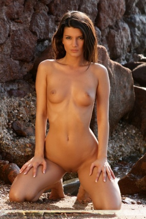 Totally naked girl Amandine C strikes great poses outside a medieval building