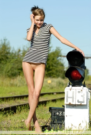 Adorable teen Amelie displays her thin body while naked on railway tracks