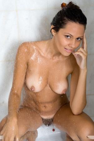 Naked brunette Chiara soaps up her long legs and trimmed bush in the shower