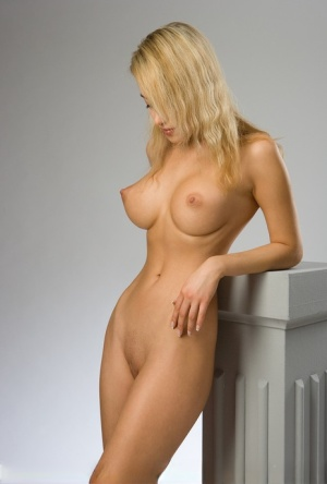 Busty beauty Lia shows off her perky big tits perching naked on a plinth