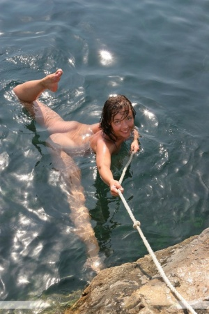 Totally naked beauty Kalinka holds a rope while slipping into the sea
