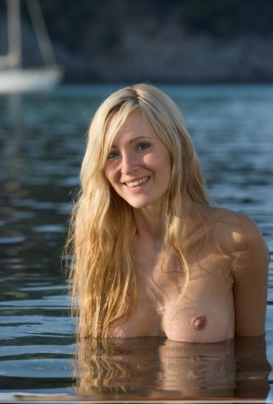 Young blonde girl Corinna stands totally naked in warm waters