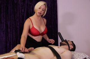 Blonde masseuse Goddess Breanna ties up a client and fits a dildo to his face