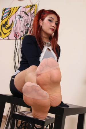 Clothed redhead removes her pantyhose covered feet from black heels