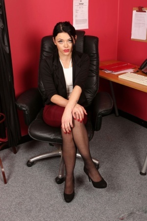 Clothed secretary Sapphire Rose flashes panties while looking at a girlie mag