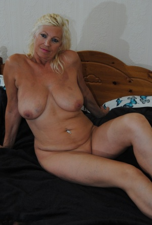 Mature fatty Platinum Blonde lounges naked to display oiled big floppy tits