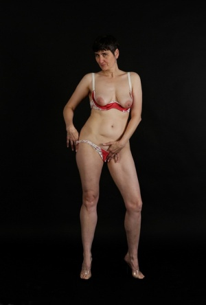 Horny granny with small saggy boobs peels red lingerie to pose naked
