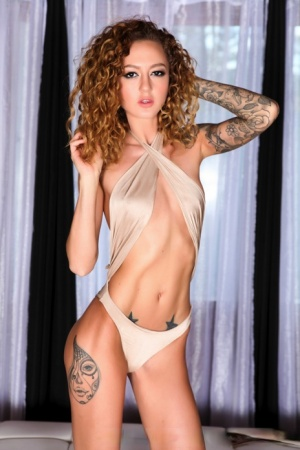 Thin girl with a tattoo sleeve Kendra Cole crosses her bare legs in heels