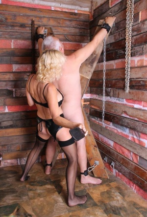Hot older ladies flog a male slave while attired in leather and latex