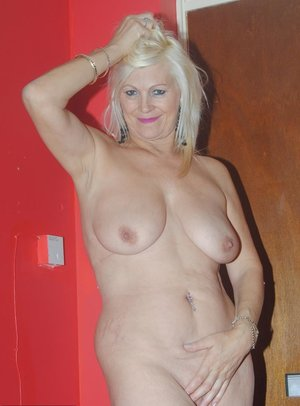 Mature amateur Platinum blonde stands naked before donning garters and nylons