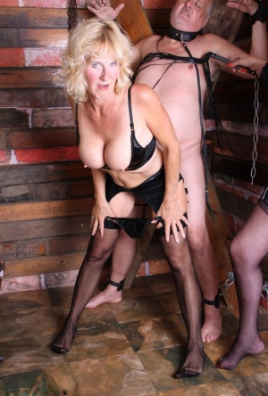 Mature blonde Dimonty and a girlfriend flog a naked man while hes restrained