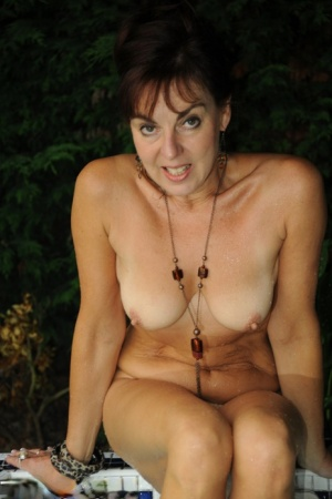 Mature lady Georgie relaxes her tan lined body in outdoor hot tub
